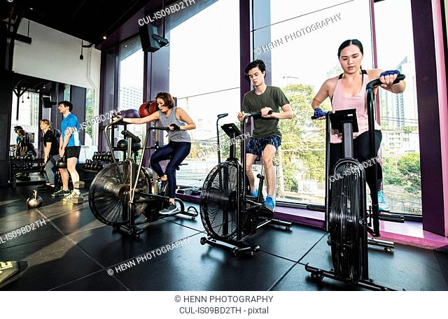 Group of people working out in gym, using exercise bikes