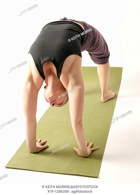 A young woman doing yoga on a green mat
