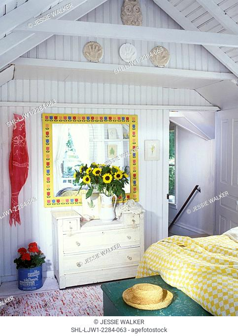 BEDROOM - Vacation home. Painted white chest, mirror with yellow frame and stylized tulips, sunflowers in white antique pitcher, straw hat