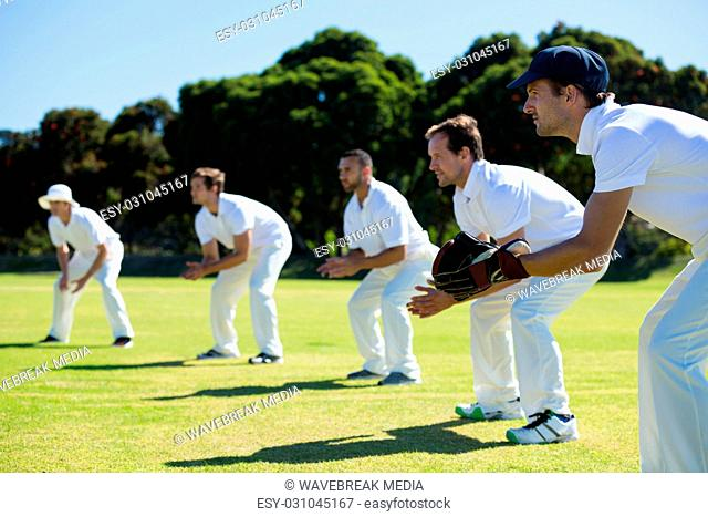 Side view of players bending while standing at grassy field