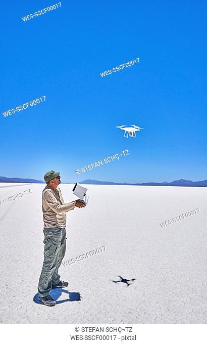Bolivia, Salar de Uyuni, man flying drone on salt lake
