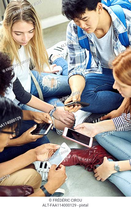 Group of students sitting together on floor, looking at smartphones