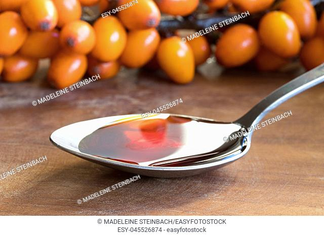 Sea buckthorn oil on a spoon with sea buckthorn branches in the background