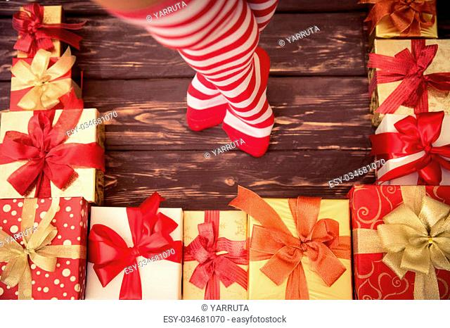Sexy Santa woman legs and gift boxes. Christmas holiday concept. Top view