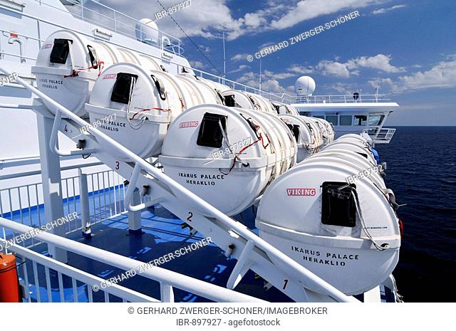 Containers holding inflatable lifeboats on the side of a ocean ferryboat, Mediterranean, Europe