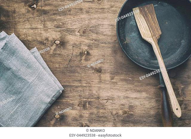 Black frying pan with a kitchen spatula, brown wood surface, empty space in the middle