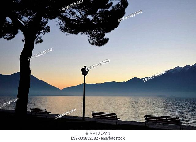 Sunset over an alpine lake with mountains and benches and a big tree