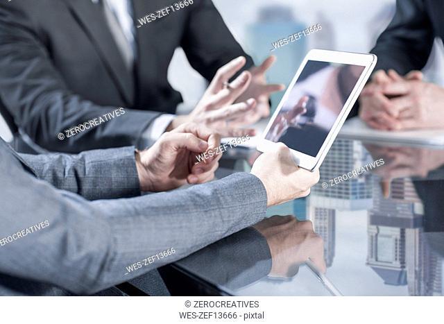 Businesspeople using tablet in meeting