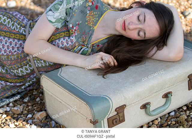 Portrait of young woman lying with suitcase on beach, Whitstable, Kent, UK
