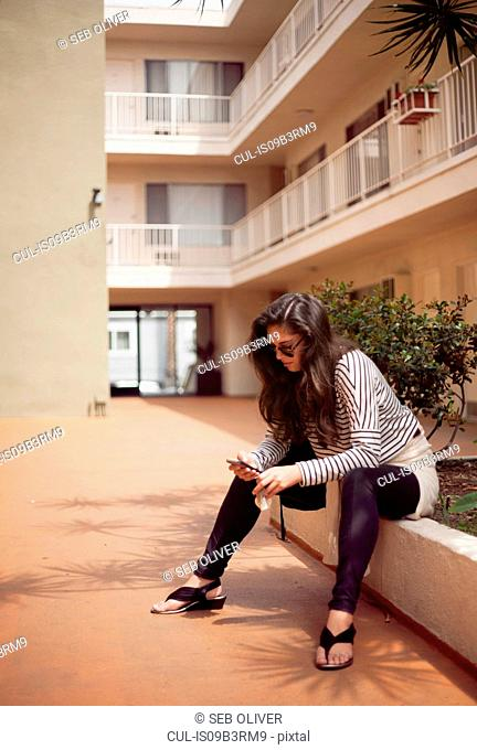 Young woman sitting on apartment wall reading smartphone texts