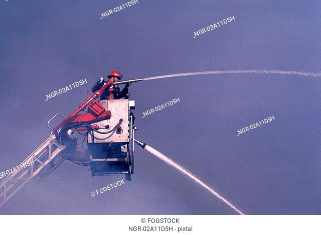 Fireman on Cherry Picker with Hose