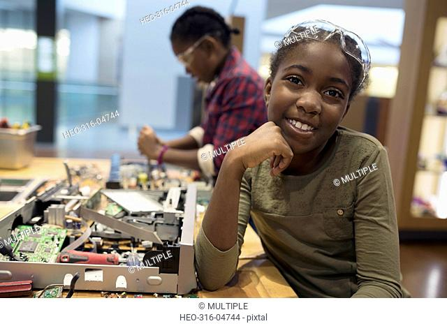 Portrait smiling girl assembling electronics in science center workshop