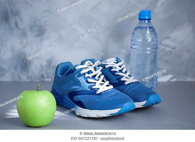 Sport shoes, apple, bottle of water on gray concrete background. Concept healthy lifestyle, sport and diet. Sport equipment