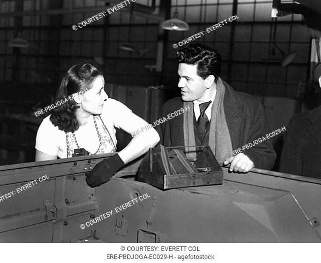Toledo war defense worker MARGARET MENDOZA, turning out jeeps for Uncle Sam, is visited by actor JOHN GARFIELD during his bond drive tour, 1943