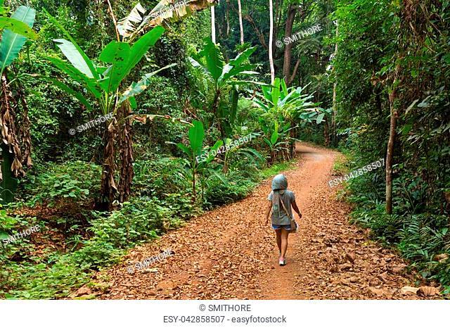 Woman walking in a lush jungle path in the Ko Kood island in Thailand
