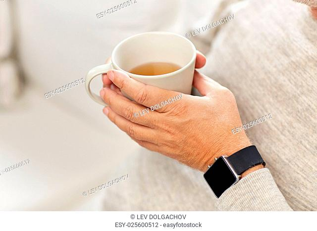 time, morning and people concept - close up of senior man with cup of tea and wristwatch at home