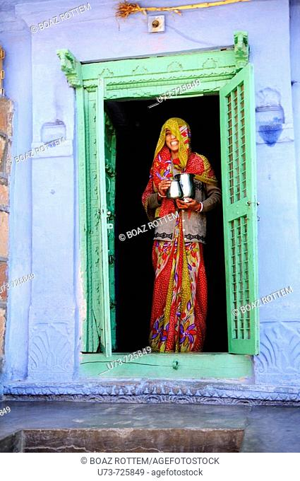 A colorful Rajasthani woman stands at the front door of her house, the house is a traditional colorful house