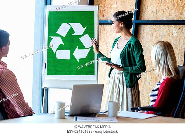 Colleagues discussing with recycling sign on white board