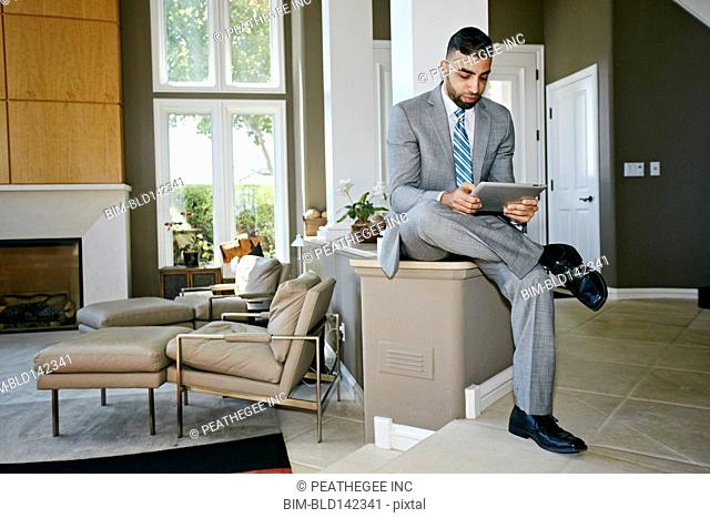 Middle Eastern businessman using digital tablet at home