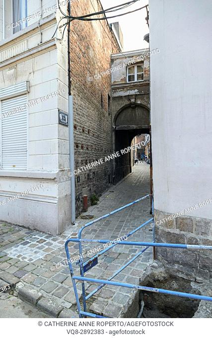Hidden alley with broken pavement leading to historic coutyard of the Beguines community of religious women, Valenciennes, France