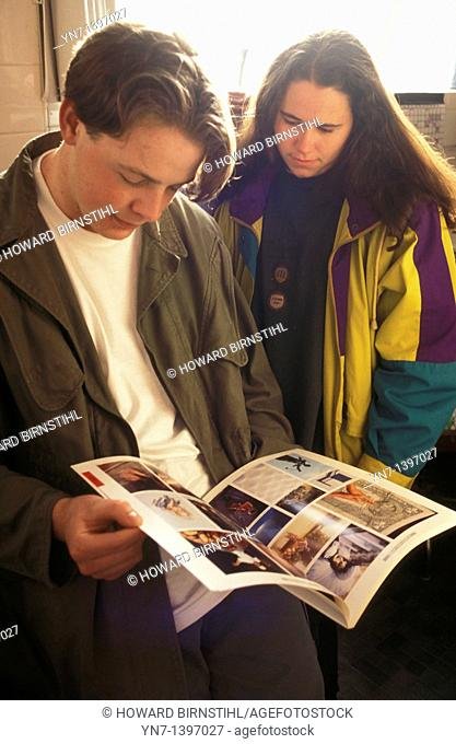 Teenage boy is engrossed in his glossy magazine while his girlfriend lends stoic support