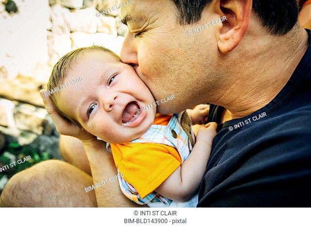 Caucasian father kissing baby boy outdoors