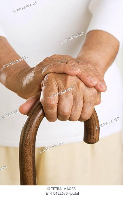 Close up of senior's hands on cane