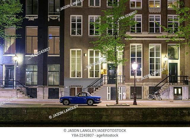 Blue car parked in front of canal houses on the Herengracht at night, Amsterdam, North Holland, Netherlands