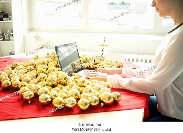 Woman sitting at table with many golden Christmas baubles working on laptop