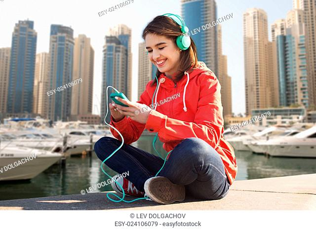 technology, lifestyle and people concept - smiling young woman or teenage girl with smartphone and headphones listening to music over dubai city street or...