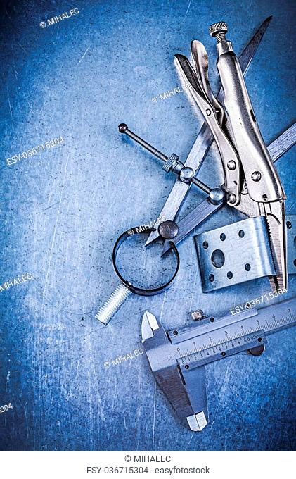 Metal lock jaw pliers trammel caliper drilled angle bars construction drawing compass on metallic background