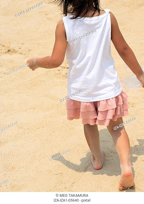 Rear view of a girl walking on the beach