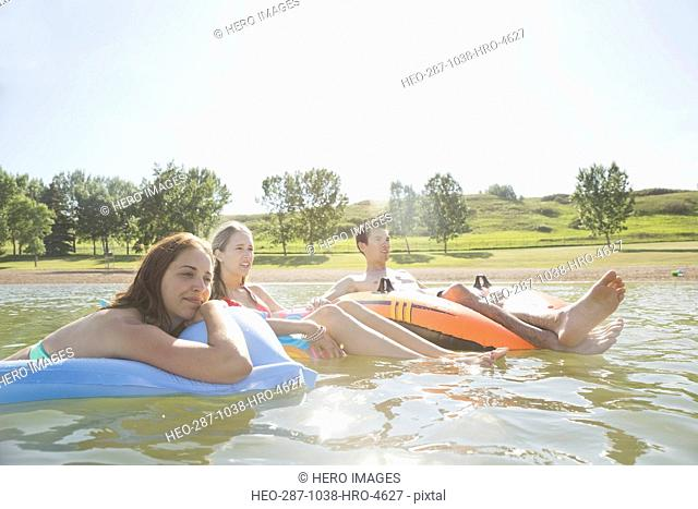 Friends floating on inflatable rafts in lake