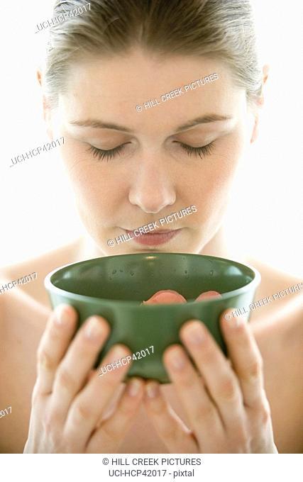 Woman smelling flower petals, green