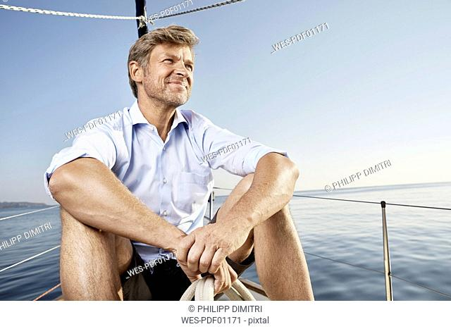 Portrait of smiling mature man sittiing on his sailing boat looking at distance
