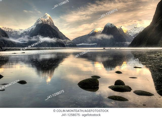 Mitre peak, winter dawn, cold mist rising from Milford Sound, Fiordland National Park