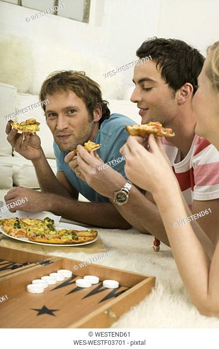 Three young people lying on floor, eating pizza