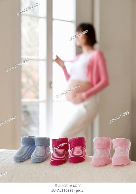 Pairs of baby booties in a row with pregnant woman in background