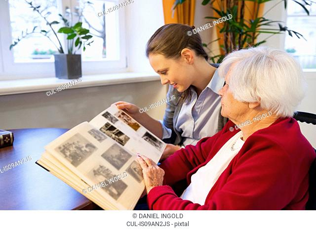 Mid adult woman and her grandmother looking at photograph album