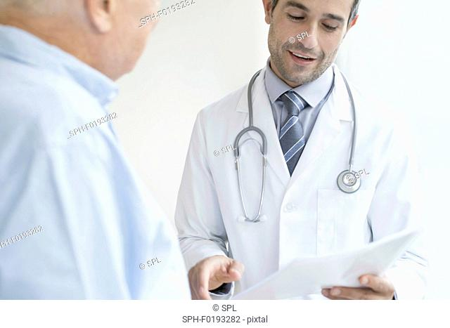 Male doctor holding medical notes