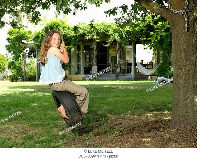 Girl swinging on tire swing in garden