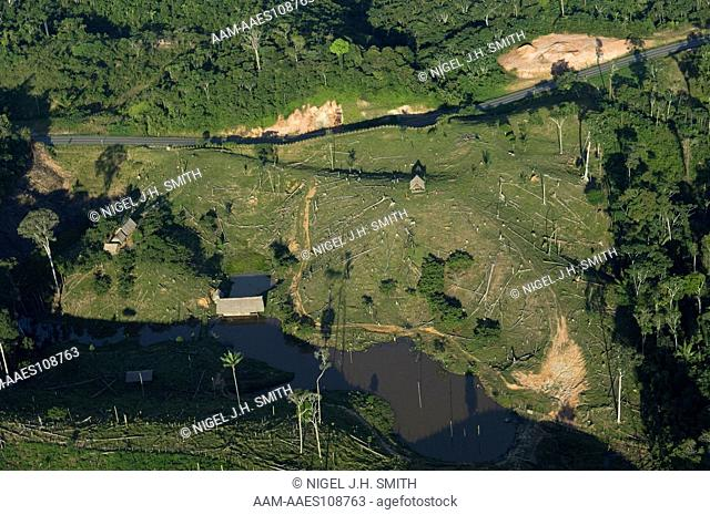 Deforestation for cattle pasture along a highway in the Peruvian Amazon. Pond created by damming stream to raise fish and to provide water for cattle