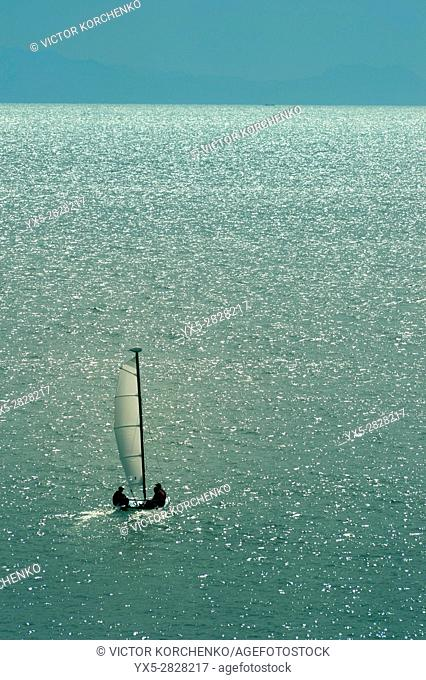 Small sail boat heading to the sea away from the shore