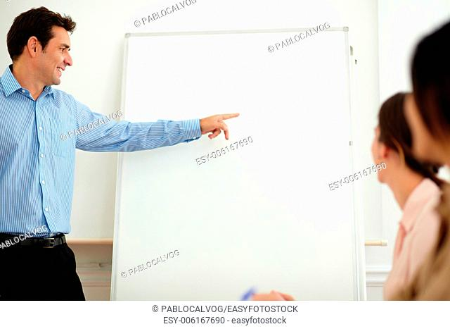 Portrait of a charming professional man pointing and looking at whiteboard while standing in front of businesswoman on office - copyspace