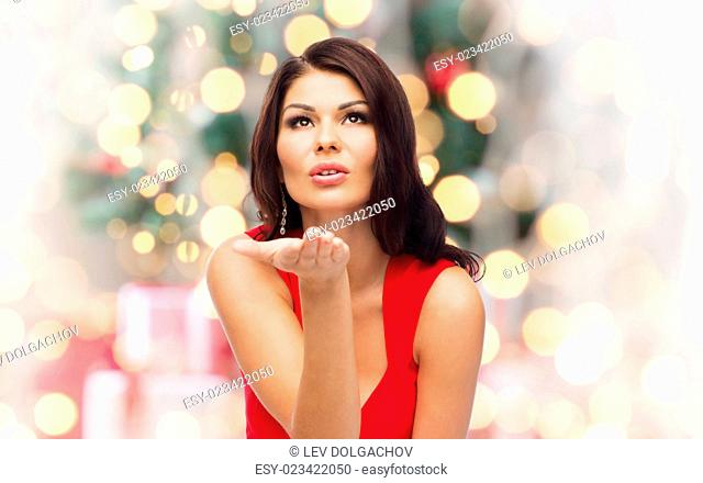 christmas, people, holidays and gesture concept - beautiful sexy woman in red dress sending blow kiss over holidays lights background