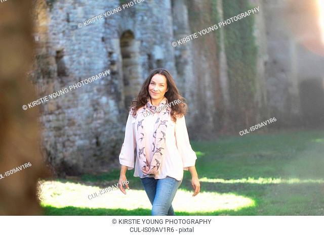 Woman strolling near walls of Thornbury Castle, South Gloucestershire, UK