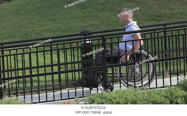 Man with spinal cord injury in a wheelchair using accessible wheelchair ramp