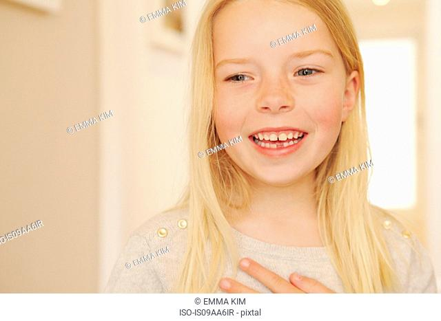 Young girl smiling, looking away