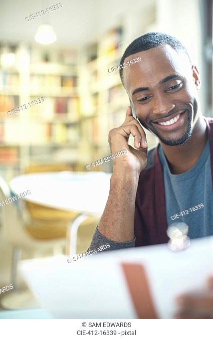 Smiling man with paperwork talking on cell phone