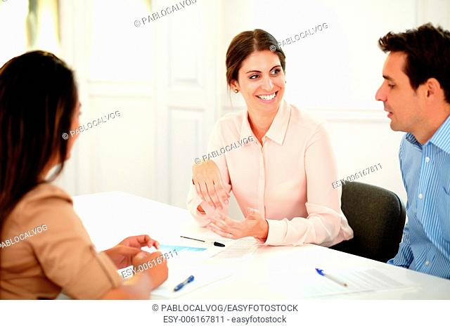 Portrait of adult professional colleagues talking and smiling while sitting on office desk